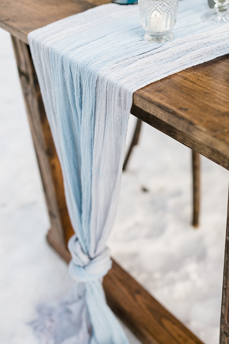 Outdoor Reception Wooden Table Blue Grey Fabric Candles Glass Holders Snowy Winter Wonderland Anniversary Shoot http://ryannlindseyphotography.com/