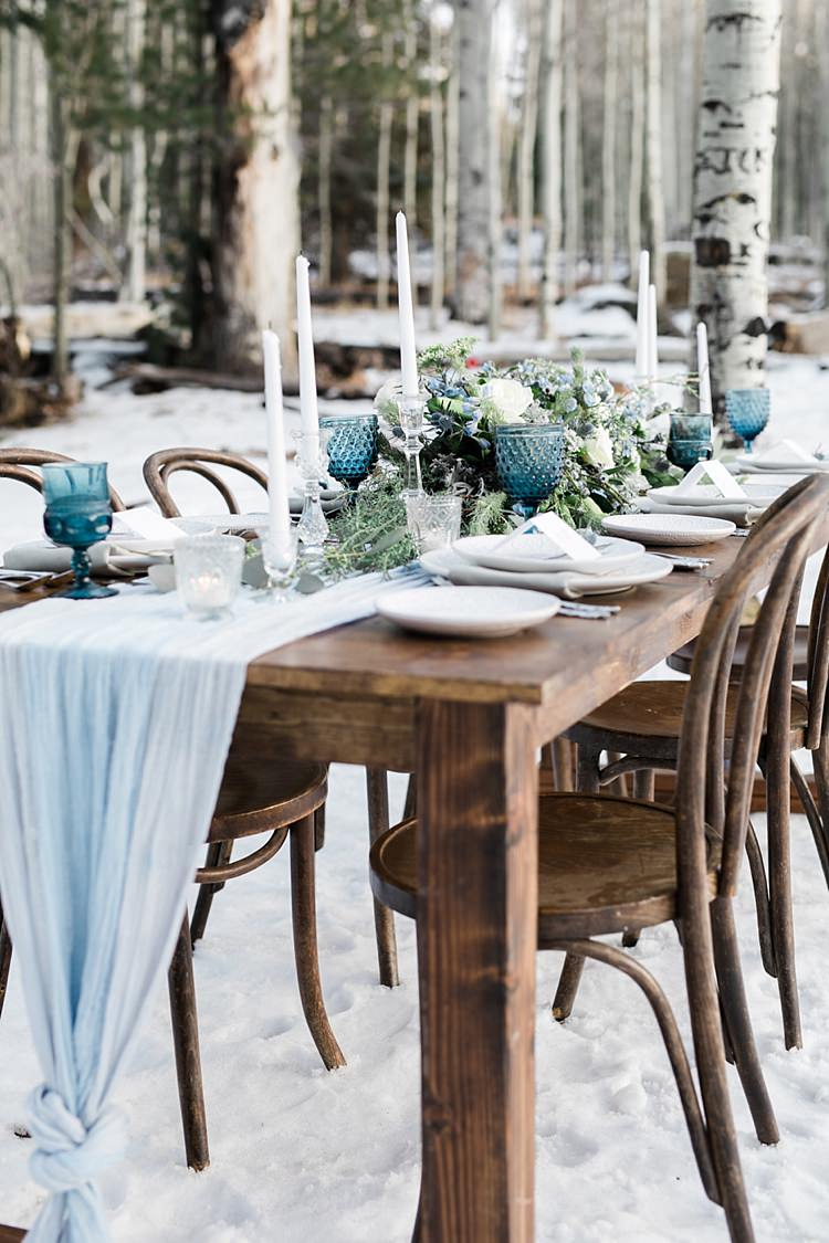 Outdoor Reception Wooden Table Blue Grey Fabric Fresh White Blue Green Flowers Blue Wine Goblets Glass Candlesticks Snowy Winter Wonderland Anniversary Shoot http://ryannlindseyphotography.com/