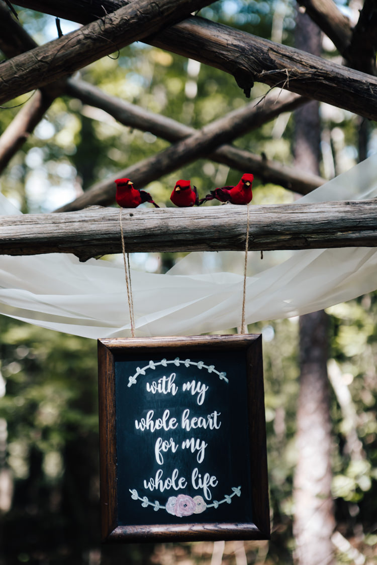 Outdoor Ceremony Decorated Wooden Arbour White Organza Red Birds DIY Quote Sign Blackboard Adventure Inspired Woodland Wedding North Carolina http://www.amandasuttonphotography.com/