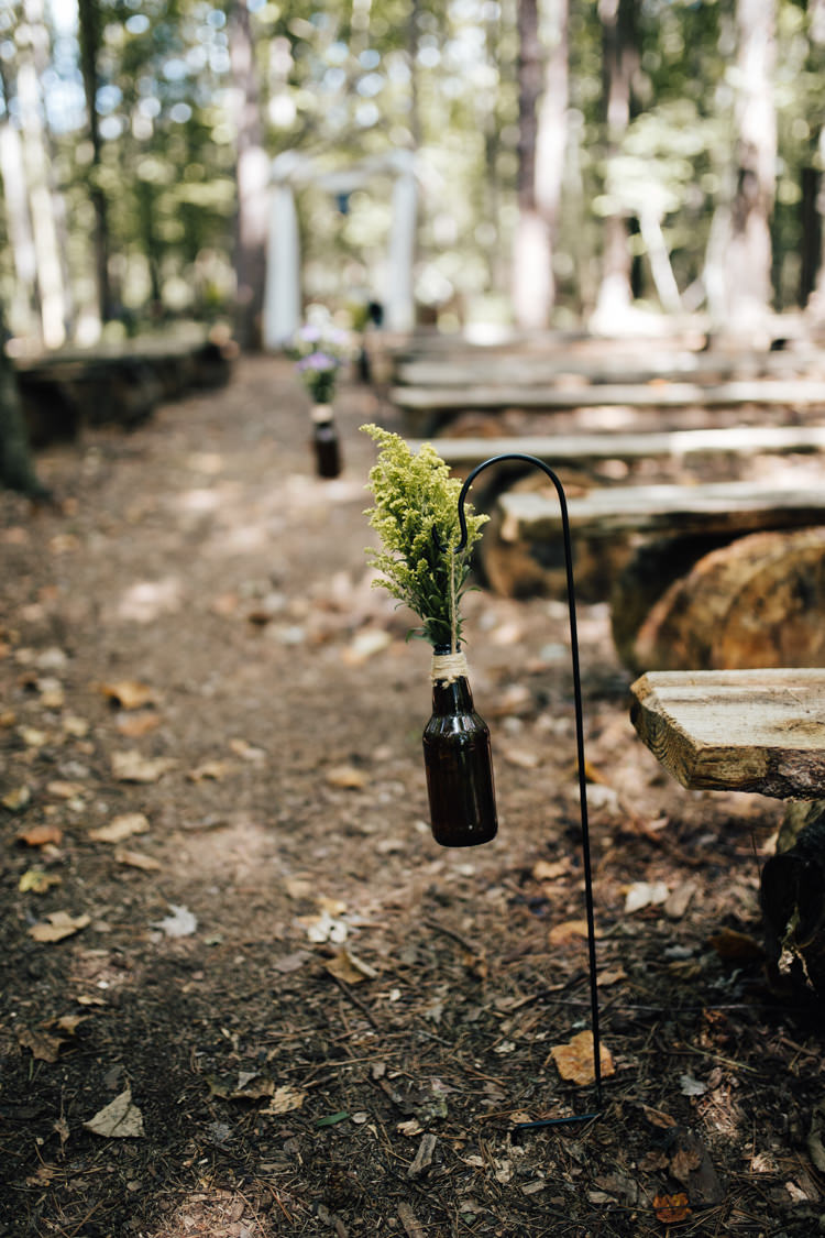 Outdoor Ceremony Wooden Bench Seating Beer Bottles Fresh Florals Twine Adventure Inspired Woodland Wedding North Carolina http://www.amandasuttonphotography.com/