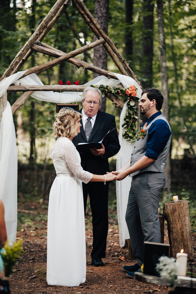 Outdoor Ceremony Bride Handmade Lace Bridal Gown Groom Grey Vest Pants Navy Blue Shirt Orange Tie Celebrant Decorated Wooden Arbour Fresh Florals Candles Adventure Inspired Woodland Wedding North Carolina http://www.amandasuttonphotography.com/