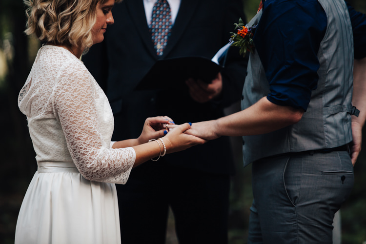 Outdoor Ceremony Bride Handmade Lace Bridal Gown Groom Grey Vest Pants Navy Blue Shirt Buttonhole Orange Florals Succulent Celebrant Ring Exchange Adventure Inspired Woodland Wedding North Carolina http://www.amandasuttonphotography.com/