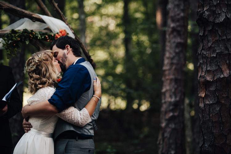 Outdoor Ceremony Bride Handmade Lace Bridal Gown Groom Grey Vest Pants Navy Blue Shirt Decorated Wooden Arbour Adventure Inspired Woodland Wedding North Carolina http://www.amandasuttonphotography.com/