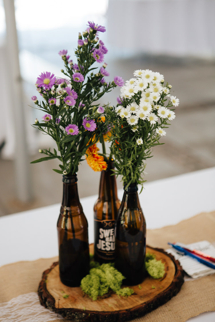 Reception Table Setting DIY Centrepieces Beer Bottles Fresh Purple White Florals Wood Slice Hessian Lace Table Runner Adventure Inspired Woodland Wedding North Carolina http://www.amandasuttonphotography.com/