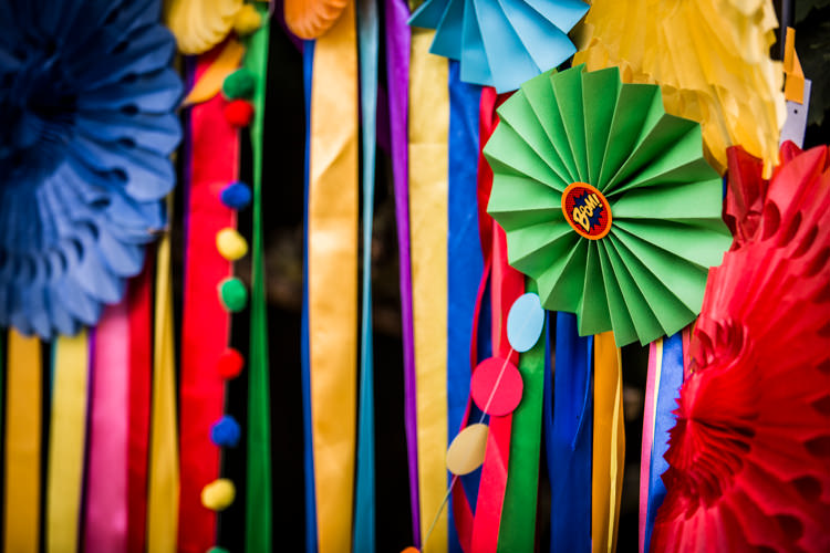 Ribbon Backdrop Pinwheels Lanterns Bunting Outdoor Rainbow Colourful Vintage Comic Book Wedding Ideas http://www.hayleypettitphotography.com/
