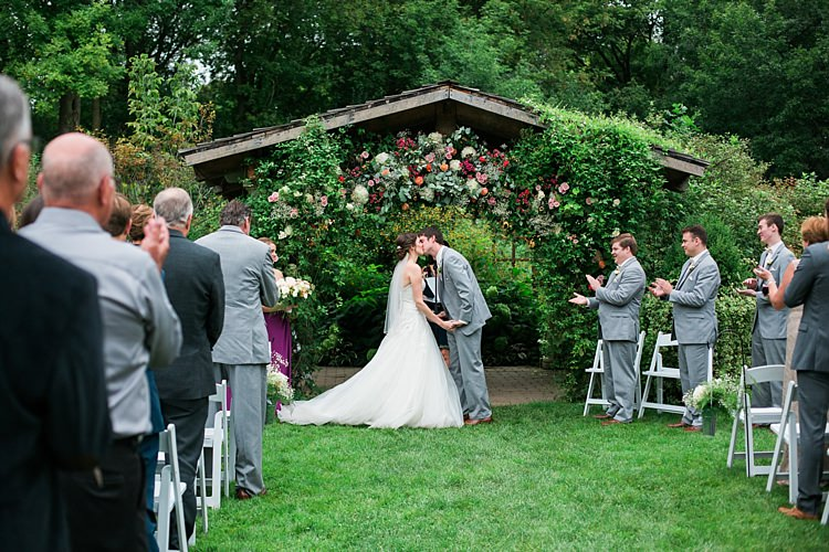 Outdoor Ceremony Bride Embellished Strapless Bridal Gown Veil Groom Light Grey Suit Guests Floral Arbour Flower Farm Outdoor Wedding Minnesota http://eileenkphoto.com/