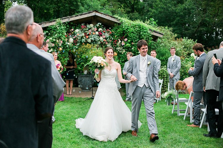 Outdoor Ceremony Bride Embellished Strapless Bridal Gown Bouquet Pale Pink White Roses Groom Light Grey Suit White Vest Tie Guests Floral Arbour Flower Farm Outdoor Wedding Minnesota http://eileenkphoto.com/