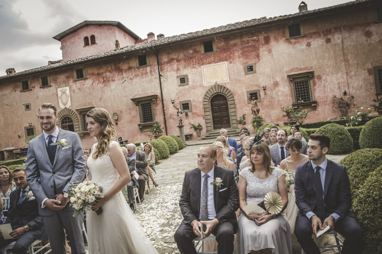 Outdoor Ceremony Bride Lace Tulle Stella York Bridal Gown Bouquet White Pink Roses Groom Light Blue Suit White Shirt Textured Blue Tie Guests Historic Pink Villa Romantic Intimate Tuscany Destination Wedding http://angelicabraccini.com/