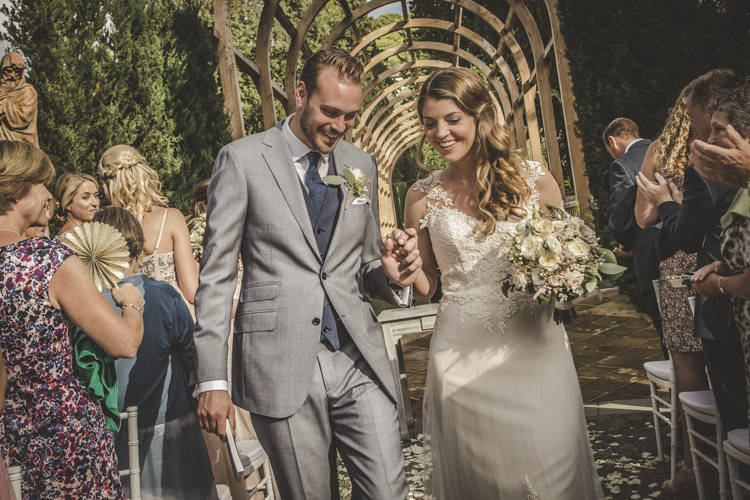 Outdoor Ceremony Bride Lace Tulle Stella York Bridal Gown Bouquet White Pink Roses Groom Light Blue Suit White Shirt Textured Blue Tie Guests Archway Green Hedges Romantic Intimate Tuscany Destination Wedding http://angelicabraccini.com/