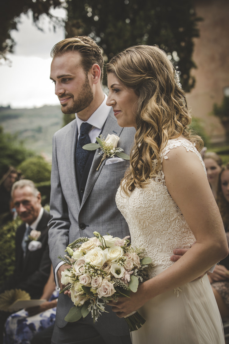 Outdoor Ceremony Bride Lace Tulle Stella York Bridal Gown Bouquet White Pink Roses Groom Light Blue Suit White Shirt Textured Blue Tie Rose Buttonhole Guests Romantic Intimate Tuscany Destination Wedding http://angelicabraccini.com/
