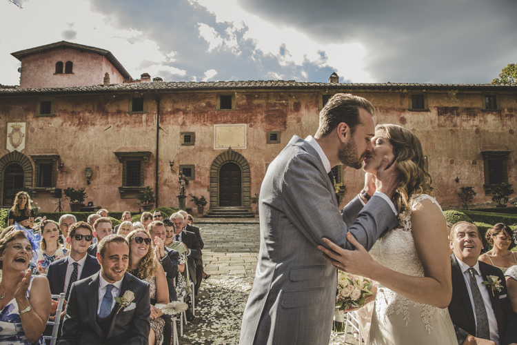 Outdoor Ceremony Bride Lace Tulle Stella York Bridal Gown Groom Light Blue Suit White Shirt Textured Blue Tie Guests Historic Pink Villa Romantic Intimate Tuscany Destination Wedding http://angelicabraccini.com/