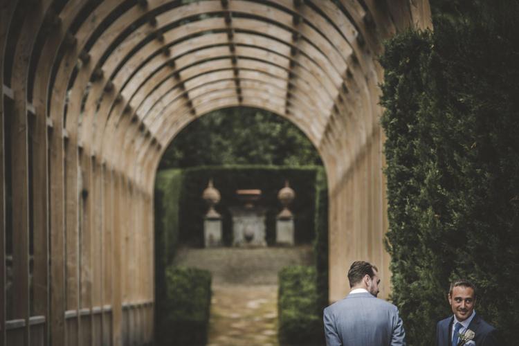 Outdoor Ceremony Groom Light Blue Suit Groomsman Archway Green Hedges Romantic Intimate Tuscany Destination Wedding http://angelicabraccini.com/