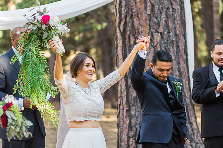 Outdoor Ceremony Bride Watters Separates Lace Top Tulle Skirt Veil Cascading Multicoloured Bouquet Groom Dark Blue Jacket Black Satin Lapel Black Pants Bowtie Celebrant DIY Whimsical Camp Wedding California http://www.landbphotography.org/