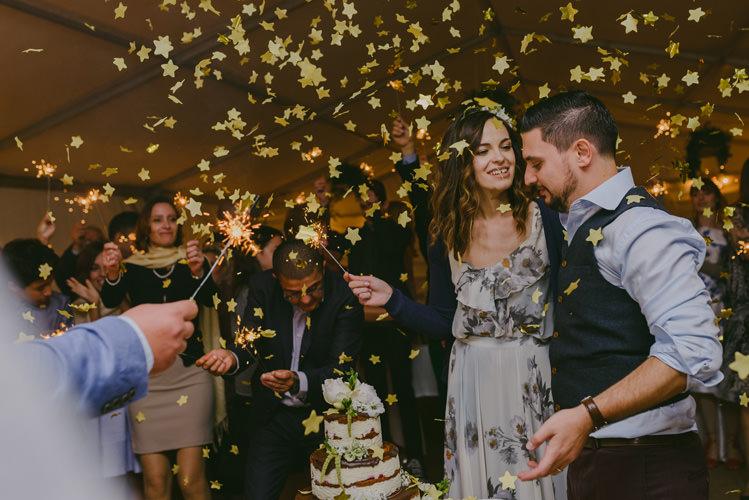 Reception Gold Confetti Sparklers Bride Patterned Floral Dress Cardigan Floral Hairpiece Groom Light Blue Shirt Dark Grey Vest Wedding Cake Guests Natural Greenery Stylish Wedding Transylvania https://raresion.com/