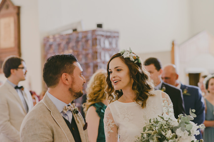 Church Ceremony Bride Two Piece Lace Bridal Gown Floral Hairpiece Bouquet White Florals Greenery Groom Light Blue Shirt Dark Grey Vest Sand Jacket Patterned Bowtie Natural Greenery Stylish Wedding Transylvania https://raresion.com/