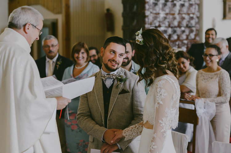 Church Ceremony Bride Two Piece Lace Bridal Gown Floral Hairpiece Groom Light Blue Shirt Sand Jacket Dark Grey Vest Brown Pants Patterned Bowtie Priest Guests Natural Greenery Stylish Wedding Transylvania https://raresion.com/