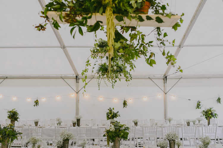 Reception Marquee White Chairs Hanging Lights Florals Greenery Natural Greenery Stylish Wedding Transylvania https://raresion.com/