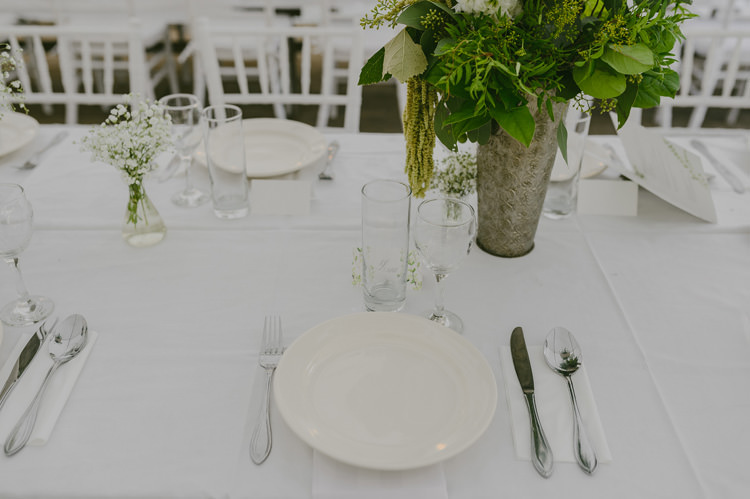 Reception Table Setting White Tablecloth Centrepiece Greenery Floral Fruit Arrangement Silver Vase Silver Cutlery Natural Greenery Stylish Wedding Transylvania https://raresion.com/