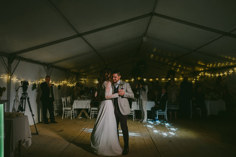 Reception White Marquee Bride Two Piece Lace Bridal Gown Groom Light Blue Shirt Sand Jacket Brown Pants Dancing Hanging Fairy Lights Natural Greenery Stylish Wedding Transylvania https://raresion.com/