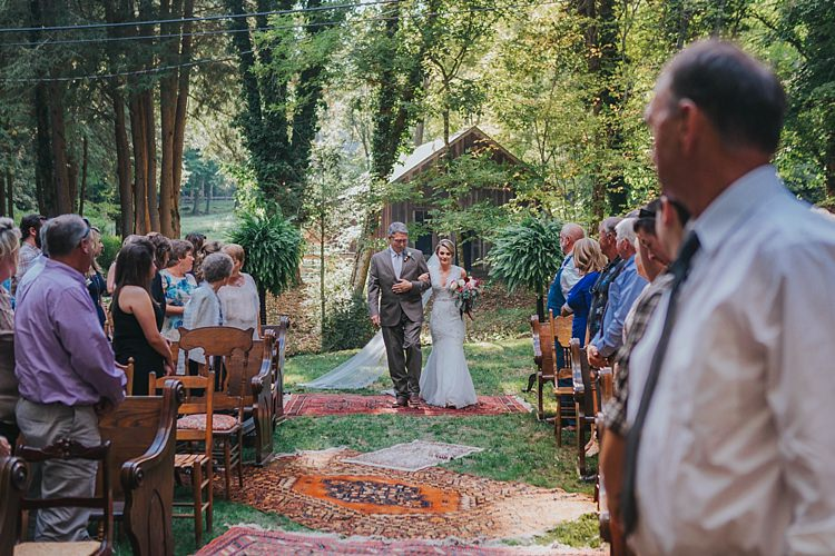 Outdoor Ceremony Bride V Neck Lace Embellished Bridal Gown Veil Multicoloured Bouquet Father Entrance Bright Rugs Guests Mismatched Wooden Chairs Bohemian & Whimsical Garden Wedding in North Carolina http://www.taylorparkerphotography.com/