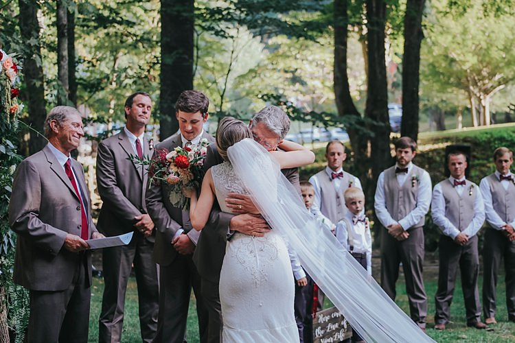 Outdoor Ceremony Bride Lace Embellished Gown Long Veil Father Groom Grey Suit Celebrant Groomsmen Floral Arch Bohemian & Whimsical Garden Wedding in North Carolina http://www.taylorparkerphotography.com/