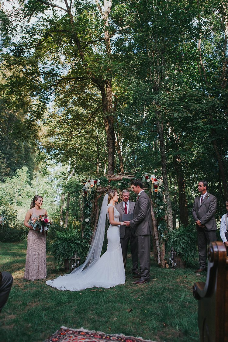Outdoor Ceremony Floral Arch Bride Lace Embellished Gown Long Veil Groom Grey Suit White Shirt Celebrant Bridal Party Bohemian & Whimsical Garden Wedding in North Carolina http://www.taylorparkerphotography.com/