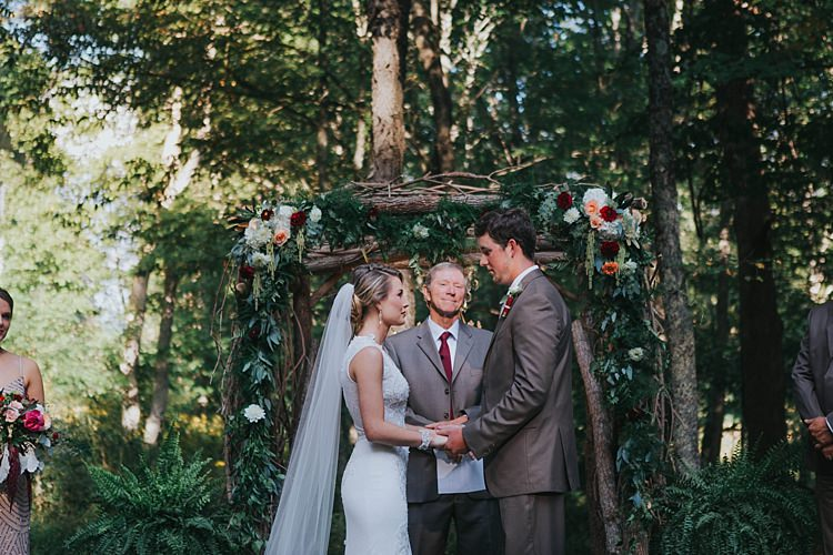 Outdoor Ceremony Floral Arch Bride V Neck Lace Embellished Gown Long Veil Groom Grey Suit White Shirt Floral Buttonhole Celebrant Bohemian & Whimsical Garden Wedding in North Carolina http://www.taylorparkerphotography.com/