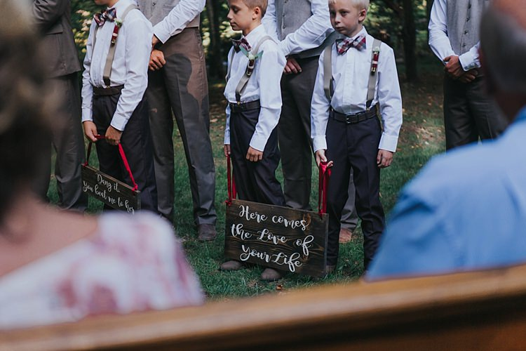 Outdoor Ceremony Page Boys Charcoal Pants White Shirts Checked Bowties Suspenders Wooden Signs Red Ribbons Bohemian & Whimsical Garden Wedding in North Carolina http://www.taylorparkerphotography.com/