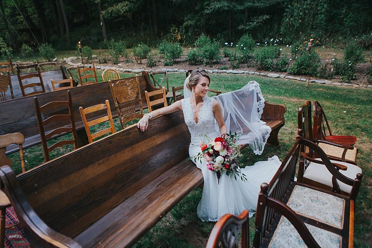 Bride V Neck Lace Embellished Bridal Gown Long Veil Multicoloured Bouquet Dahlia Garden Rose Florals Greenery Mismatched Wooden Chairs Pews Bohemian & Whimsical Garden Wedding in North Carolina http://www.taylorparkerphotography.com/