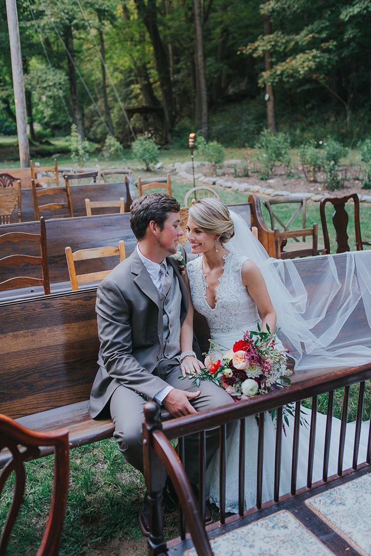 Bride V Neck Lace Embellished Bridal Gown Long Veil Multicoloured Bouquet Groom Grey Suit White Shirt Light Grey Tie Vest Mismatched Wooden Chairs Pews Bohemian & Whimsical Garden Wedding in North Carolina http://www.taylorparkerphotography.com/