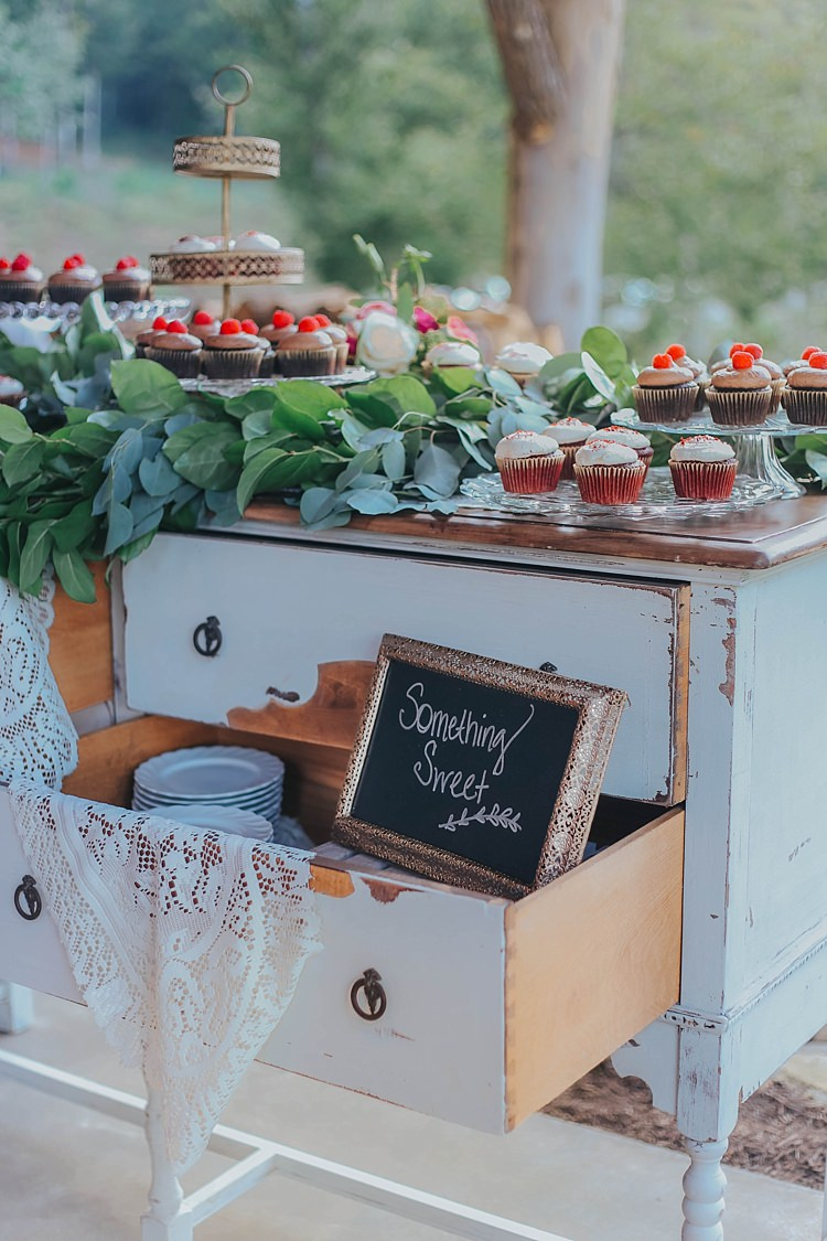Reception Dessert Table White Antique Dresser Lace Tablecloth Blackboard Sign Gold Frame Cupcakes Gold Stand Greenery Bohemian & Whimsical Garden Wedding in North Carolina http://www.taylorparkerphotography.com/