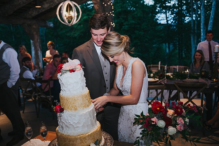 Reception Wedding Cake Cutting White Gold Sparkle Icing Multicoloured Florals Bride V Neck Lace Embellished Gown Groom Grey Suit White Shirt Light Grey Tie Vest Guests Bohemian & Whimsical Garden Wedding in North Carolina http://www.taylorparkerphotography.com/