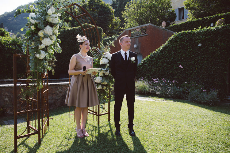Outdoor Ceremony Groom Black Tailored Suit Black Tie Floral Buttonhole Celebrant Rusted Arch White Cream Florals Greenery Botanical Copper Greenery Lake Como Wedding http://margheritacalatiphotography.com/