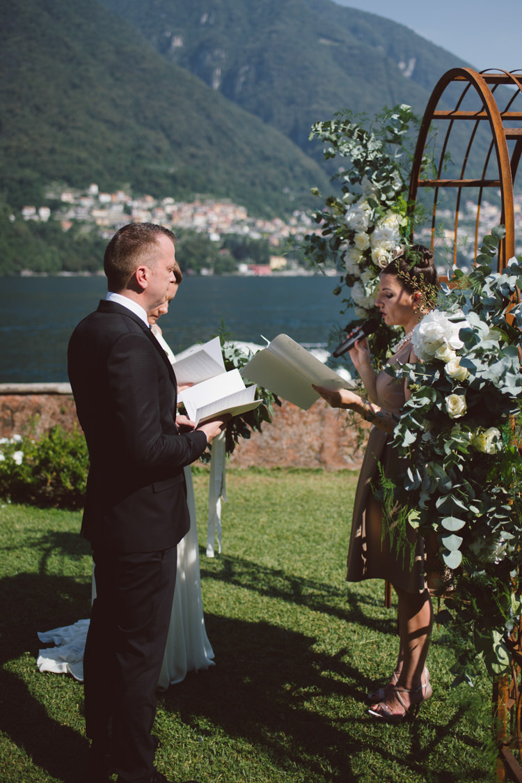 Outdoor Ceremony Bride V Neck Jenny Packham Bridal Gown Groom Tailored Black Suit White Shirt Celebrant Rusty Arch White Cream Florals Greenery Lake View Botanical Copper Greenery Lake Como Wedding http://margheritacalatiphotography.com/