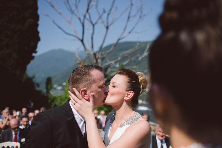 Outdoor Ceremony Bride V Neck Jenny Packham Embellished Bridal Gown Groom Tailored Black Suit White Shirt Black Tie Floral Buttonhole Kiss Guests Botanical Copper Greenery Lake Como Wedding http://margheritacalatiphotography.com/