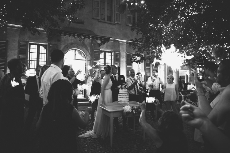 Reception Cake Cutting Bride V Neck Jenny Packham Embellished Bridal Gown Groom Tailored Black Suit Guests Fairy Lights Botanical Copper Greenery Lake Como Wedding http://margheritacalatiphotography.com/