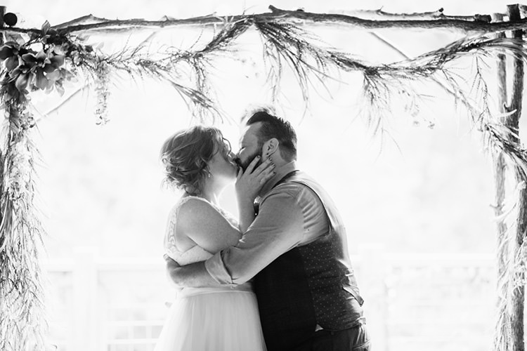 Indoor Barn Ceremony Bride Lace Tulle Bridal Gown Groom Light Grey Shirt Custom Vest Floral Arch The Kiss Creative Quirky Rustic Barn Wedding Tennessee http://www.alexbeephoto.com/