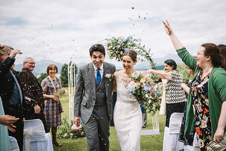 Confetti Shot Ceremony Kiss Jenny Packham Bride Bridal Steven Purvis Bespoke Groom Prince of Wales Check Archway Pink Blue Stocks Hydrangeas Greenery Bouquet Scenic Outdoor Loch Lomond Wedding http://www.lisadevinephotography.co.uk/