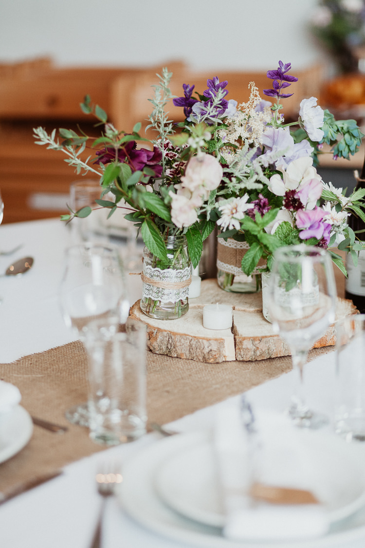 Centrepiece Decor Table Jars Hessian Lace Flowers Log Beautifully Relaxed Outdoorsy Barn Wedding http://www.caitlinandjones.co.uk/