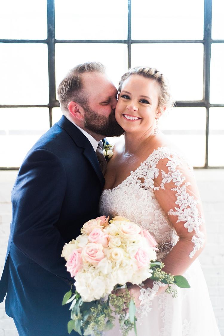 Bride Groom Kiss Cheek Lace Sleeves Romantic Industrial Studio Loft Georgia Wedding http://krisandraevans.com/