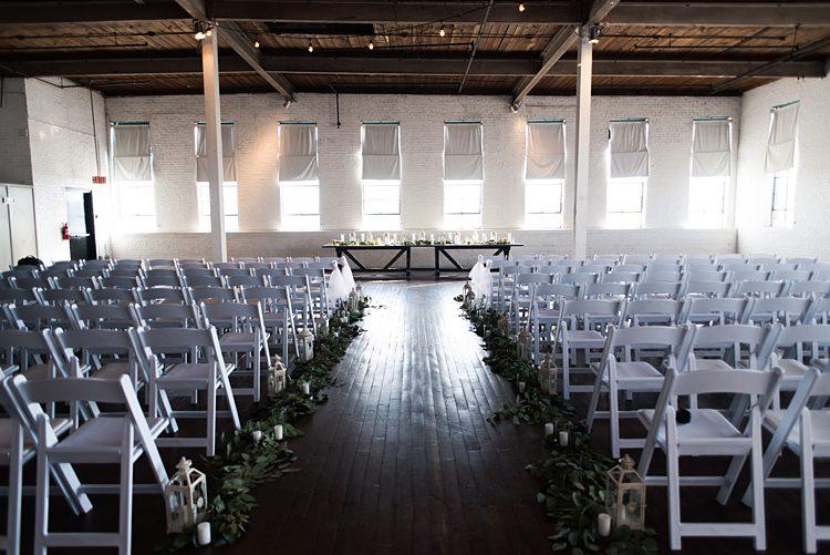Ceremony White Chairs Lanterns Aisle Romantic Industrial Studio Loft Georgia Wedding http://krisandraevans.com/