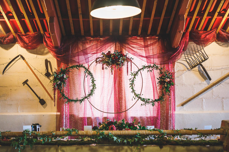 Floral Hoop Red Voile Runner Foliage Greenery Rustic Barn Red Gold Glam Wedding https://garethnewsteadphotography.com/