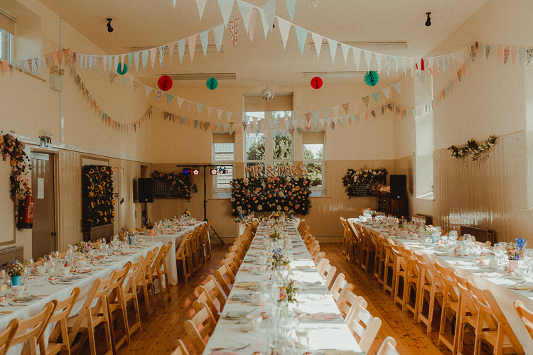 Village Hall Flower Wall Bunting Lanterns Long Tables Eclectic Kitsch Retro Fete Wedding http://www.belleartphotography.com/