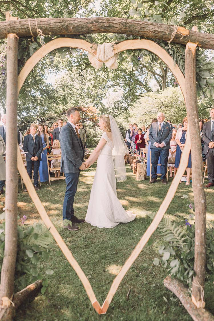 Ceremony Backdrop Wooden Heart Tree DIY Homemade Kate Walker Bride Dress Gown Moss Bros Tweed Groom Relaxed Outdoor Marquee Farm Wedding http://www.jenniferjanephotography.co.uk/