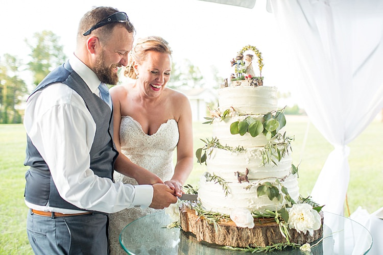 Cutting Cake Rustic Figurines Topper Pets White Tiers Flowers Greenery Intimate Farmhouse Wedding South Carolina https://jessicahuntphotography.com/