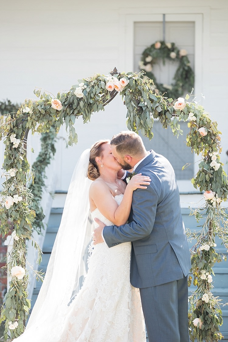 Groom Grey Suit Blue Tie Bride Long Veil Lace Dress Sweetheart Neckline Outdoor Ceremony Archway Greenery Kiss Archway Intimate Farmhouse Wedding South Carolina https://jessicahuntphotography.com/