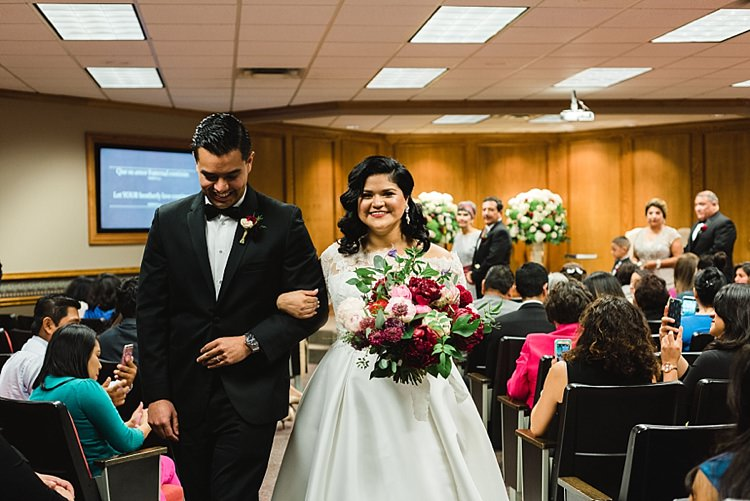 Bride Groom Aisle Recession Bowtie Lace Dress Off Shoulder Sleeves Bouquet Red Pink Peonies Roses Greenery Modern Romantic Winter Wedding Texas http://www.albarosephotography.com/
