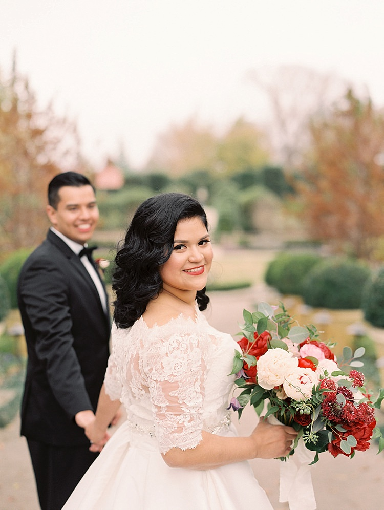 Bride Groom Garden Bowtie Lace Dress Off Shoulder Sleeves Bouquet Red Pink Peonies Roses Greenery Modern Romantic Winter Wedding Texas http://www.albarosephotography.com/