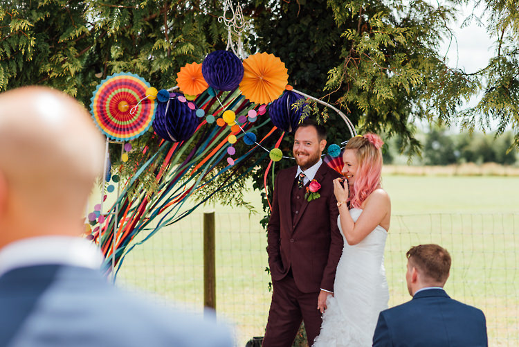 Ceremony Arch Backdrop Ribbons Pinwheels Pom Poms Alternative Colourful Outdoor Humanist Village Hall Wedding http://www.chebirchhayesphotography.com/