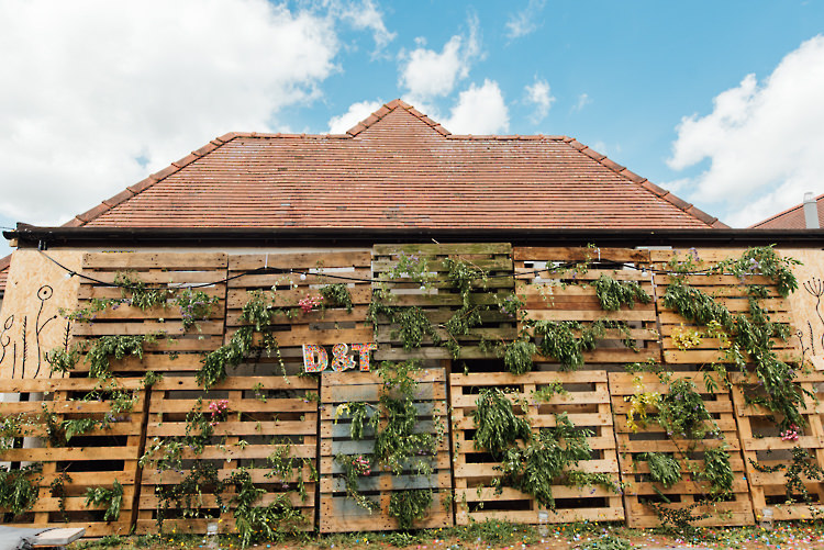 Foliage Greenery Wall Wooden Pallet Festoon Lights Alternative Colourful Outdoor Humanist Village Hall Wedding http://www.chebirchhayesphotography.com/